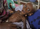 """Mihag Gedi Farah, a seven-month-old child with a weight of 3.4kg,  is held by his mother in a field hospital of the International Rescue Committee, IRC, in the town of  Dadaab, Kenya, Tuesday, July 26, 2011. The U.N. will airlift emergency rations this week to parts of drought-ravaged Somalia that militants banned it from more than two years ago, in a crisis intervention to keep hungry refugees from dying along what an official calls the """"roads of death."""" Tens of thousands already have trekked to neighboring Kenya and Ethiopia, hoping to get aid in refugee camps.(AP Photo/Schalk van Zuydam)"""