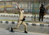 Srinagar: A police man throws stones towards protesters to disperse them during clashes in Srinagar on Wednesday. PTI Photo (PTI8_24_2016_000231B)