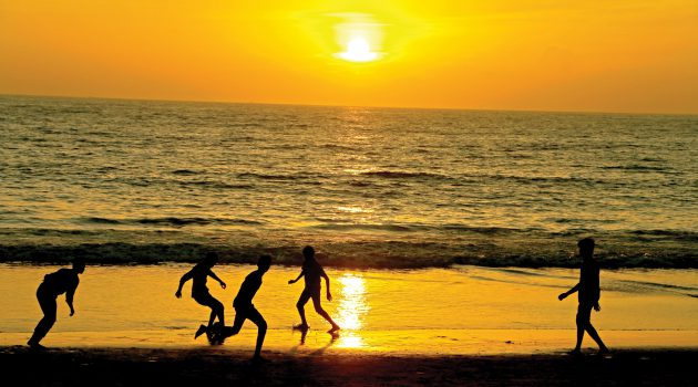 yungsters-playing-foot-ball-under-sunset-beach