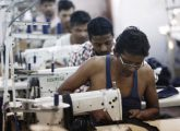 Employees sew clothes at a garment factory in New Delhi