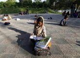 Children study between their classes at a local park in Islamabad